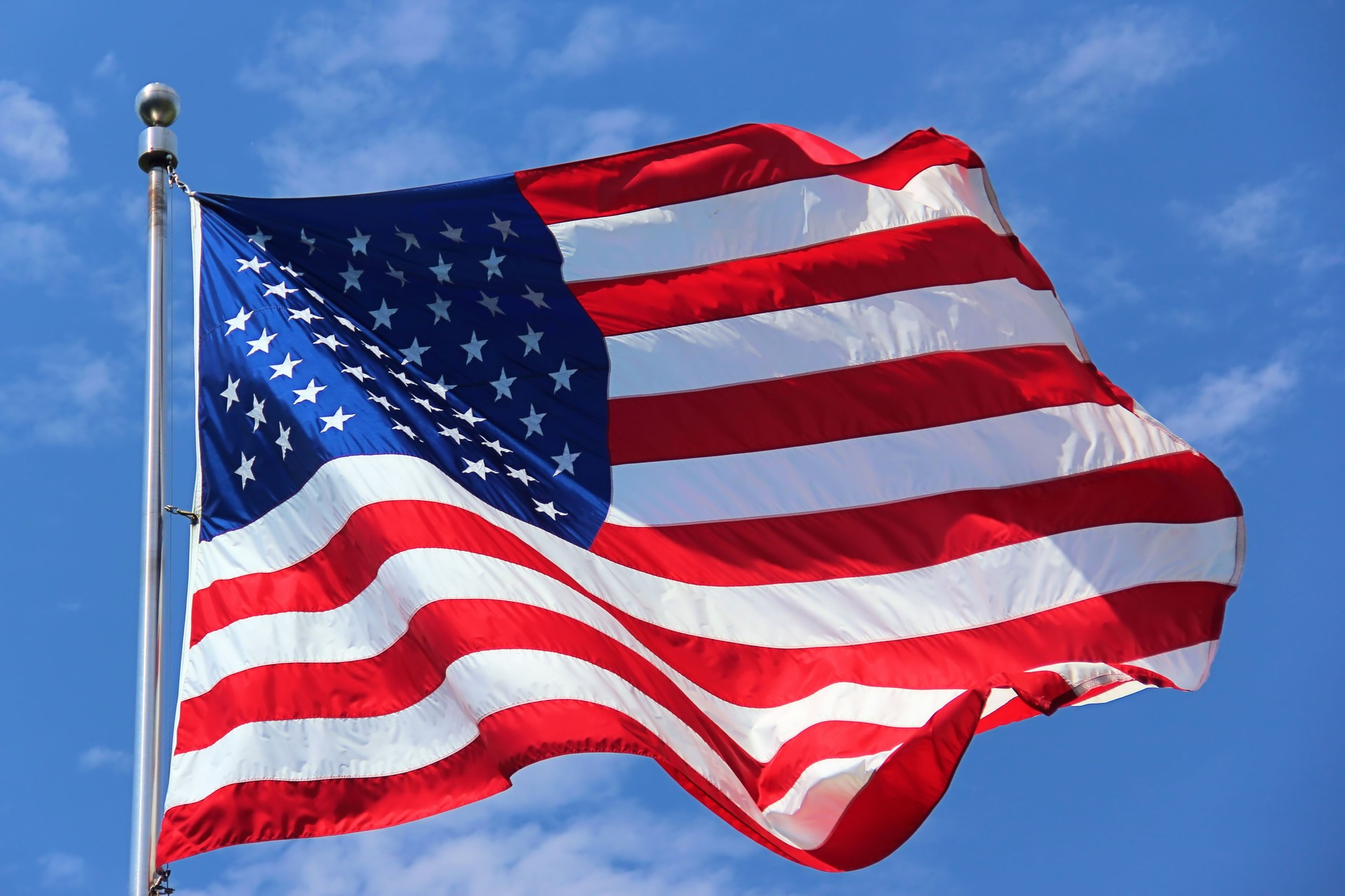 american flag waving against a blue sky